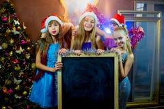 Groupe de jeunes filles célébrant Noël Panneau noir Images libres de droits