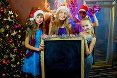 Groupe de jeunes filles célébrant Noël Panneau noir Photographie stock