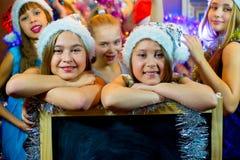 Groupe de jeunes filles célébrant Noël Panneau noir Images stock