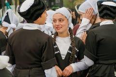 Groupe de jeunes filles dansant parler avec des garçons dans des costumes traditionnels pendant la partie Image stock