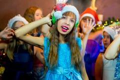 Groupe de jeunes filles gaies célébrant Noël écouteurs Photo stock