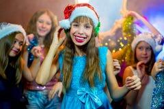 Groupe de jeunes filles gaies célébrant Noël écouteurs Photos libres de droits