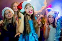 Groupe de jeunes filles gaies célébrant Noël écouteurs Photographie stock