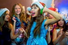 Groupe de jeunes filles gaies célébrant Noël écouteurs Photo libre de droits