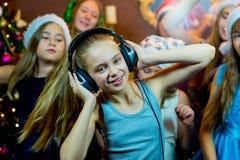 Groupe de jeunes filles gaies célébrant Noël écouteurs Image stock