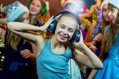 Groupe de jeunes filles gaies célébrant Noël écouteurs Image libre de droits