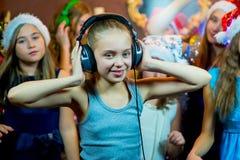 Groupe de jeunes filles gaies célébrant Noël écouteurs Images stock