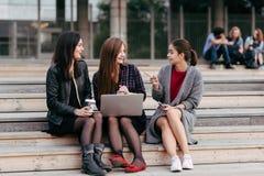 Groupe de jeunes filles ou étudiantes de hippie parlant entre eux tout en se reposant avec le filet-livre portatif sur un campus, Photo libre de droits