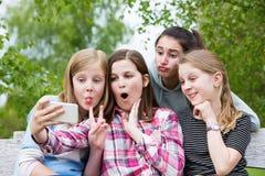Groupe de jeunes filles posant pour Selfie en parc Photos libres de droits