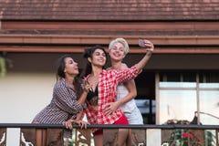 Groupe de jeunes filles sur la terrasse prenant la photo de Selfie au téléphone intelligent de cellules, belle communication d'am Photos stock