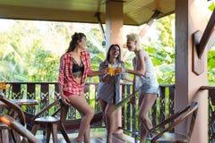 Groupe de jeunes filles sur le jus parlant de boissons de terrasse d'été, belle lumière naturelle de communication de femme dehor Photo stock