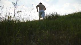 Groupe de jeunes hommes courant la colline verte au-dessus du ciel bleu avec la fusée du soleil au fond Les athlètes masculins pu Image stock
