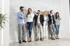 Groupe de jeunes hommes d'affaires élégants se tenant contre le mur Photos libres de droits