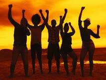 Groupe de jeunes hommes et de femmes ayant la partie à la plage sur le coucher du soleil Image stock
