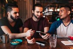 Groupe de jeunes hommes de métis à l'aide du téléphone et parlant dans la barre de salon Amis du Moyen-Orient ayant l'amusement e Photographie stock libre de droits