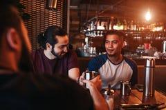 Groupe de jeunes hommes de métis buvant du thé dans la barre de salon Amis du Moyen-Orient ayant l'amusement en café Photos libres de droits