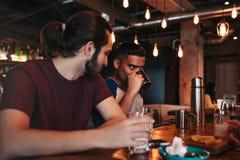 Groupe de jeunes hommes de métis buvant du thé dans la barre de salon Amis multiraciaux ayant l'amusement en café Photographie stock