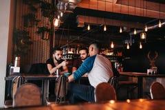 Groupe de jeunes hommes de métis parlant dans la barre de salon Amis multiraciaux ayant l'amusement en café Photo stock