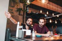 Groupe de jeunes hommes de métis parlant dans la barre de salon Amis multiraciaux ayant l'amusement en café Image libre de droits