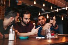 Groupe de jeunes hommes de métis parlant dans la barre de salon Amis multiraciaux ayant l'amusement en café Photo libre de droits