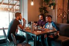 Groupe de jeunes hommes de métis parlant dans la barre de salon Amis multiraciaux ayant l'amusement en café Image stock