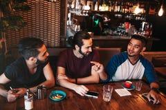 Groupe de jeunes hommes de métis parlant dans la barre de salon Amis multiraciaux ayant l'amusement en café Photos stock