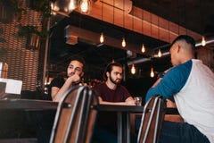 Groupe de jeunes hommes de métis parlant dans la barre de salon Amis multiraciaux passant le temps en café Photos libres de droits
