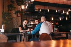 Groupe de jeunes hommes de métis parlant dans la barre de salon Amis multiraciaux traînant et ayant l'amusement en café Photographie stock
