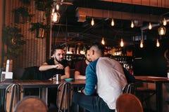 Groupe de jeunes hommes de métis parlant et riant dans la barre de salon Amis multiraciaux ayant l'amusement en café Photographie stock