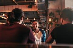 Groupe de jeunes hommes de métis parlant et riant dans la barre de salon Amis multiraciaux ayant l'amusement en café Image libre de droits