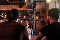 Groupe de jeunes hommes de métis parlant et riant dans la barre de salon Amis multiraciaux ayant l'amusement en café Les types tr Photos libres de droits