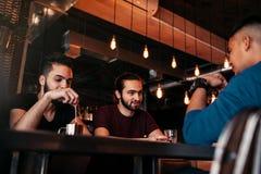 Groupe de jeunes hommes de métis parlant et riant dans le restaurant Amis multiraciaux ayant l'amusement en café Repaire de types Photos stock