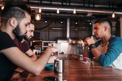 Groupe de jeunes hommes de métis parlant et riant dans le restaurant Amis multiraciaux ayant l'amusement en café Repaire de types Photographie stock libre de droits