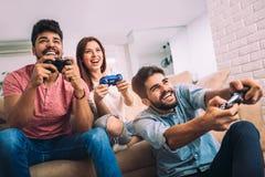 Groupe de jeunes jeux vidéo de jeu d'amis ensemble Photographie stock libre de droits
