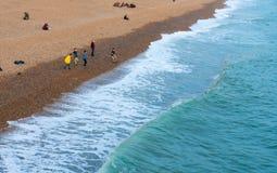 Groupe de jeunes pierres de lancement et sautantes de garçon à travers l'eau chez Brighton Pier Beach photos stock