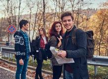 Groupe de jeunes randonneurs se tenant sur les lignes de touche de route à la belle forêt d'automne, type avec la hausse de plani photos libres de droits