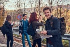 Groupe de jeunes randonneurs se tenant sur les lignes de touche de route à la belle forêt d'automne, type avec la hausse de plani image stock