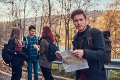 Groupe de jeunes randonneurs se tenant sur les lignes de touche de route à la belle forêt d'automne, type avec la hausse de plani photo libre de droits