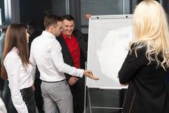 Groupe de jeunes sûrs de bisiness analysant des données utilisant le panneau de bureau image libre de droits