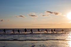 Groupe de jeunes surfers sur la plage Photo stock