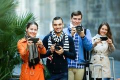 Groupe de jeunes touristes avec des appareils-photo Photos libres de droits