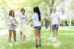 Groupe de jeunes volontaires prenant des ordures en parc Photos stock