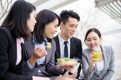 Groupe de l'équipe d'affaires ayant la salade en dehors du bureau photos stock