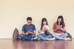 Groupe de l'étudiant universitaire asiatique à l'aide du comprimé et du téléphone portable  images stock