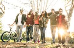 Groupe de la bande urbaine d'amis marchant en parc de patin de ville Photos stock