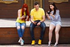 Groupe de la jeunesse jouant le jeu vidéo mobile dehors Photos libres de droits