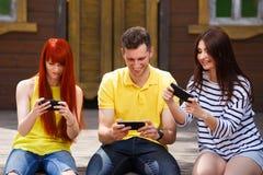 Groupe de la jeunesse riant dépendant à jouer l'OU mobile de jeu vidéo image stock