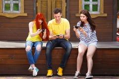 Groupe de la jeunesse riant jouant le jeu vidéo mobile dehors Photographie stock libre de droits