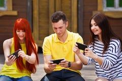 Groupe de la jeunesse riant jouant le jeu vidéo mobile dehors Photographie stock
