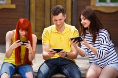 Groupe de la jeunesse riant jouant le jeu vidéo mobile dehors Photo libre de droits